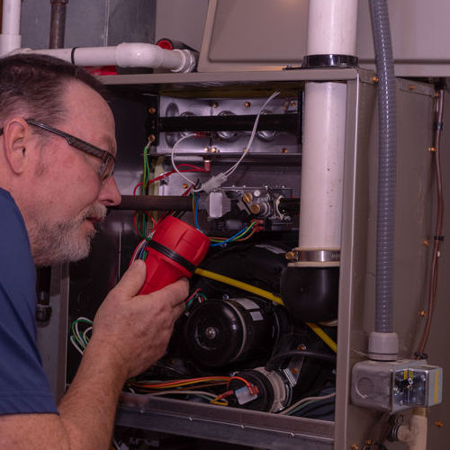 A Technician Checks a Gas Furnace.