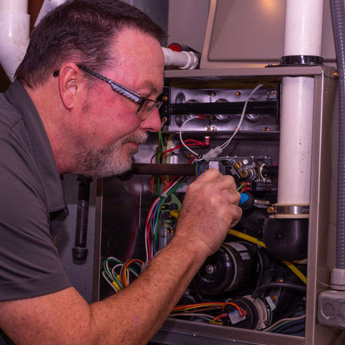 A Technician Works on a Gas Furnace Repair.