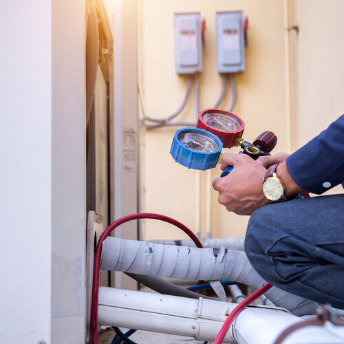 A Technician Services an Air Conditioner.