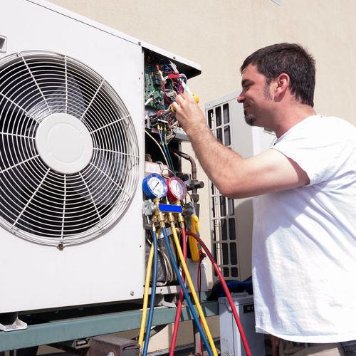 An HVAC Technician Works on an AC.