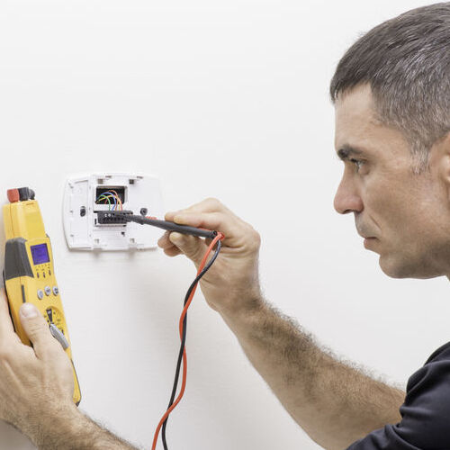 A Technician Tests a Thermostat.