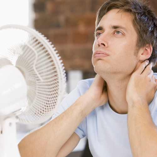 A Man Tries Cool Off With Fan